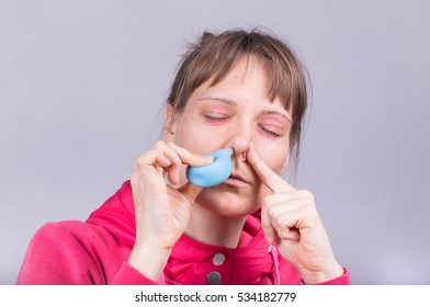 Woman with Swollen, Red Eyes Cleaning Her Blocked Nose with a Blue Rubber Nose Pump