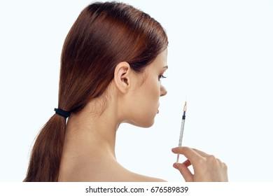 Woman with syringe on isolated background