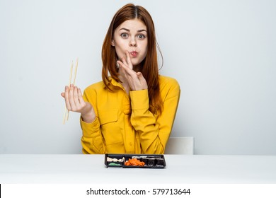 The woman at the table with bright rolls on a light background, Asian food