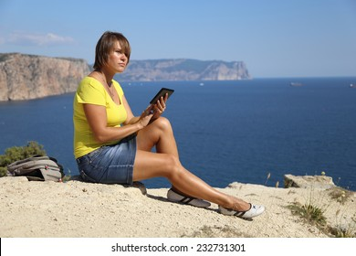 woman with tablet computer on the beautiful coast