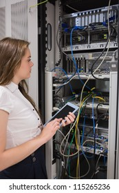 Woman with a  tablet pc looking at the servers in data center