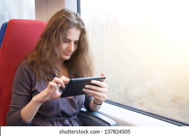 A woman with a tablet pc on a train ride