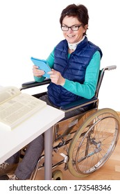Woman with Tablet PC's in a wheelchair at the table