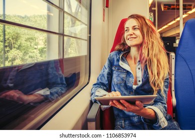 Woman with tablet traveling by pablic transport. Beautiful young female travelling in a train and looking through the window