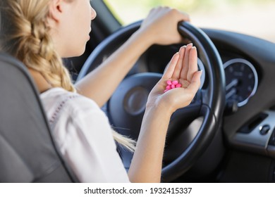 woman with tablets while steering the car