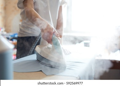 Woman tailor ironing textile with steaming on the iron board before starting work