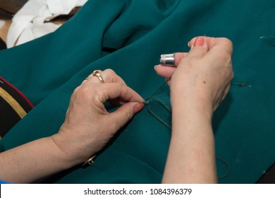 A woman tailor sews buttons to a military uniform with a needle with a thread and a thimble on her finger