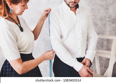 Woman tailor takes measures with male models. Mid section portrait of tailor fitting bespoke suit to model