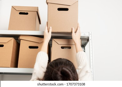 Woman take a cardboard box from a shelf of a rack in warehouse close up. Clean up and organize a pantry concept.
