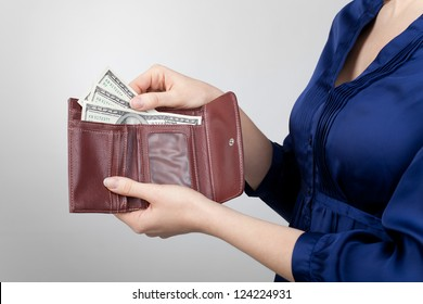 Woman take dollar money out from wallet.