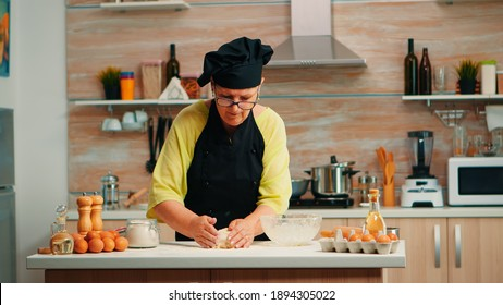 Woman take dough out of glass bowl and put it on the table for kneading. Retired elderly baker with bonete mixing ingredients with wheat flour preparing dough for baking homemade cake and bread