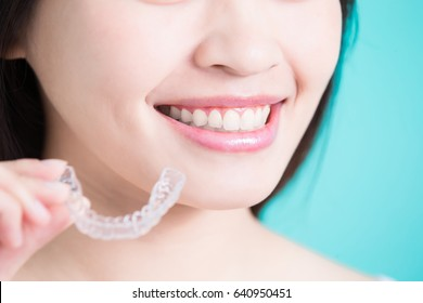 woman take invisible braces on the green background
