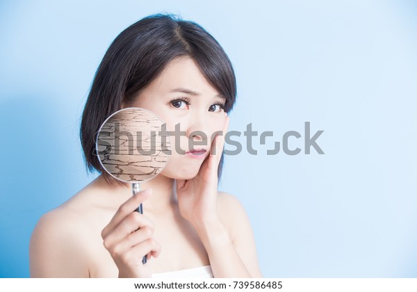 woman take magnifying with dry skin on the blue background