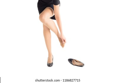 woman take off her highheel tight shoe and mass her weary bare foot, black classic dress and shoes, isolated on white, close up
