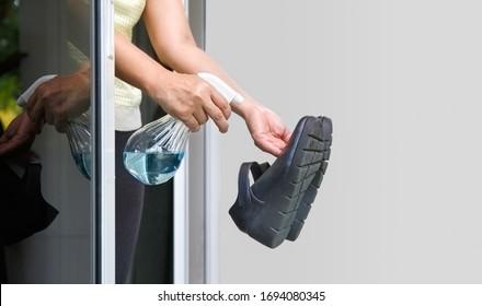 Woman take off her shoes and clean with alcohol before entering a house for protect infected from Covid-19