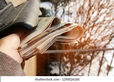 woman take off the  pile of newspapers from the mail box