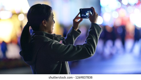 Woman take photo on mobile phone in the street at night