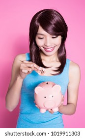woman take piggy bank and bitcoin on the pink background