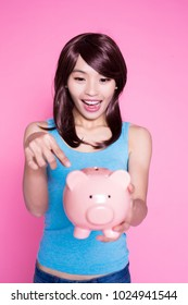 woman take piggy bank and show something on the pink background