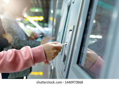 Woman take a train ticket after buy from subway ticket machine. Transportation concept