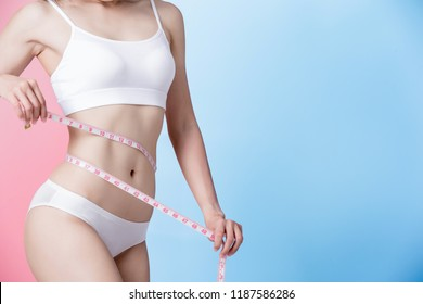 woman take waist scale tape show her thin waist with blue and pink background