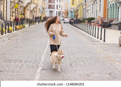 The woman take a walk with husky dog at sunny autumn day on old European city street. Horizontal view.