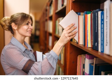 Woman takes book from shelf in university library