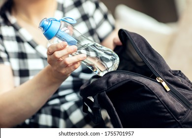 Woman takes the bottle out from backpack. Woman takes the reusable bottle of fresh water with carbon filter out from her backpack.