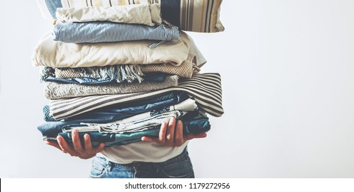 Woman takes in hands big pile laundry