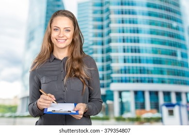 Woman takes notes on clipboard