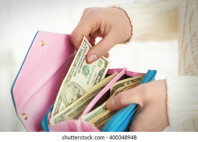 Woman takes out money from a blue wallet
