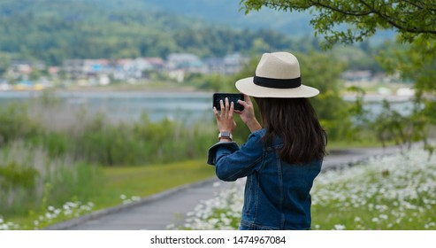 Woman takes photo with cellphone in countryside