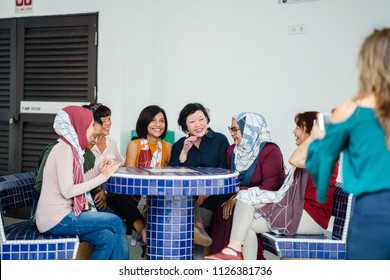 A woman takes a photo of her friends sitting and chatting around a chess table in the day. They are from different ethnicities and cultures (Malay and Chinese) and are old friends talking.