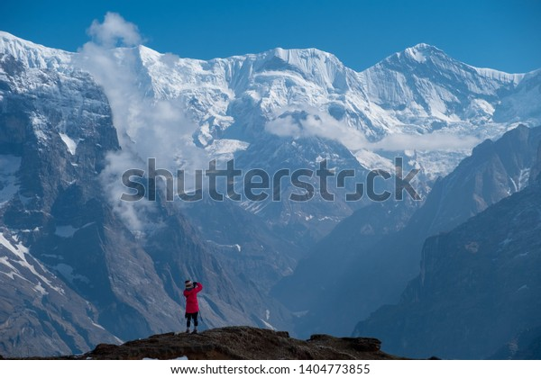A woman takes a photo from the upper view point of the Mardi Himal trek in the Annapurna Conservation Area.