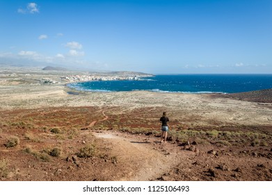 Woman takes photos of El Medano bay from mountain Roja. Spain, Canary islands, Tenerife.