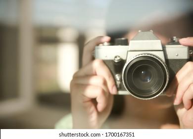 A woman takes photos with a retro camera