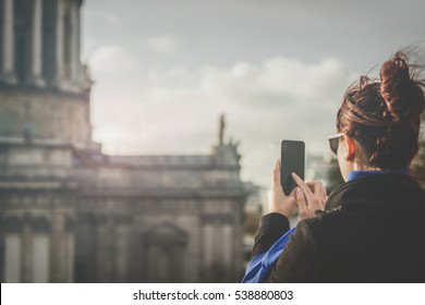 Woman takes photos with smartphone of a landmark