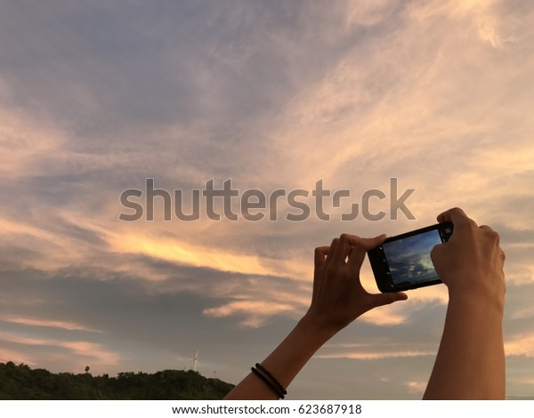 a woman takes a picture of the beautiful twilight sky by her mobile phone with far away white windmill on the top of the hill background on her great holiday