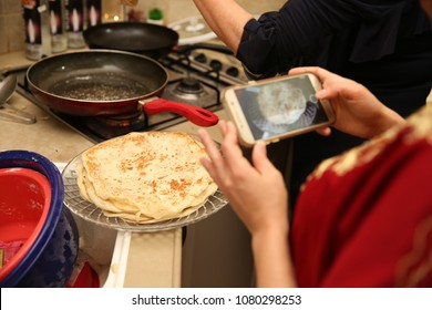 """Woman takes picture with cell phone of another woman frying Jewish Moroccan traditional food called """"mufleta"""""""