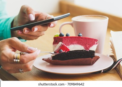 Woman takes a picture of cup with cappuccino and a piece of dessert on the plate, soft focus background