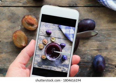 Woman takes picture of plum jam and fresh plums