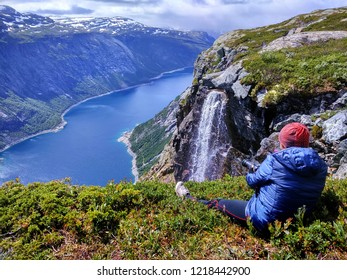 Woman takes picture of Ringedalsvatnet lake on the way to Trolltunga, Norway