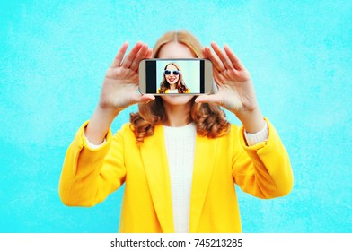 woman takes picture self portrait on smartphone on blue background