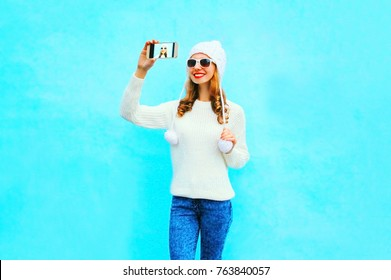 woman takes a picture self portrait in white knitted sweater, hat on a smartphone on blue background
