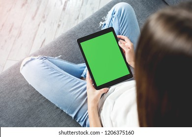 Woman takes a rest on sofa with digital tablet computer. Clipping path included.