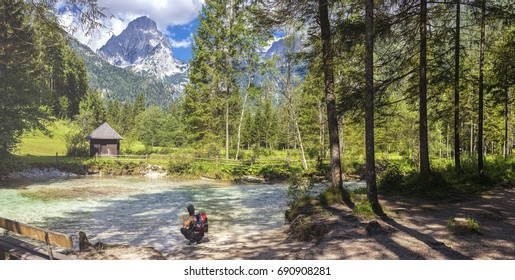 Woman takes a rest at the river Krumme Steyr in Hinterstoder with a view at the mountain Spitzmauer. Hinterstoder is in Upper Austria and especially known for his famous world cup ski races in winter.