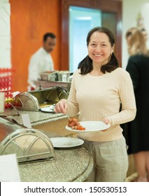 Woman takes sausages on the buffet table