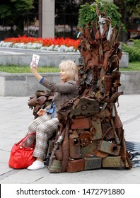 a woman takes a selfie on mobile phone sitting on art object from parts of missiles and shells on a street  in Kiev, Ukraine, 1 August 2019.