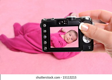 woman takes snapshot of a small one week old newborn baby girl on a pink background