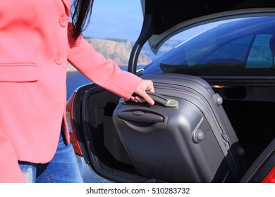 Woman takes suitcase from the car trunk. Arrived on vacation at a resort